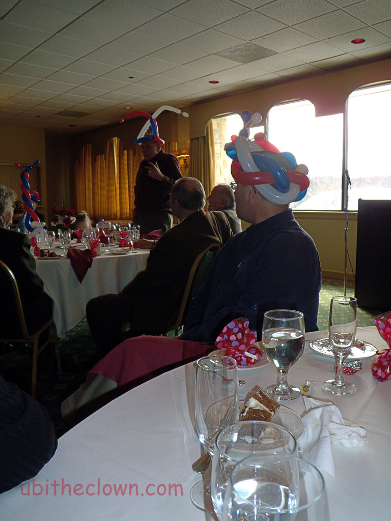 Balloon hats at an 80th birthday party. The guest of honor is speaking.