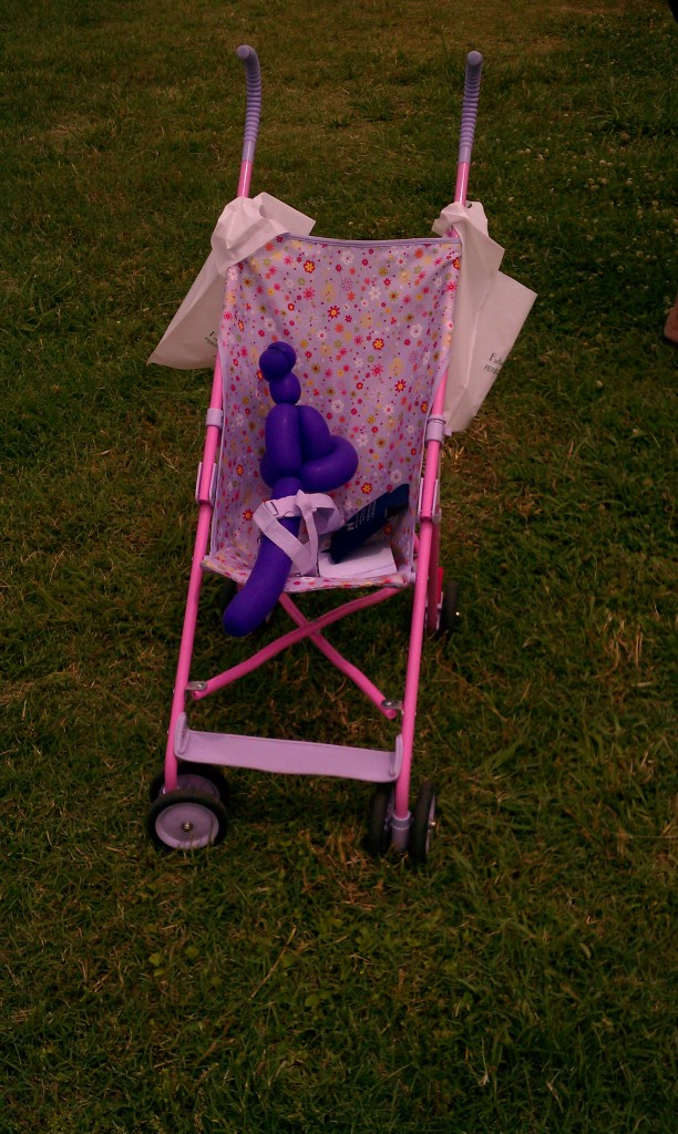 A child parked her balloon animal in her stroller while she played with a hoop.