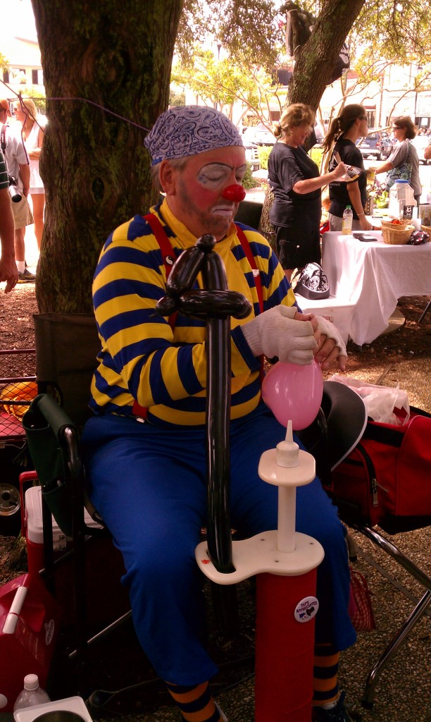 The pirate clown makes a sword balloon.