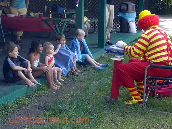 Children settled down to watch some clown magic after the swimming part of the party.