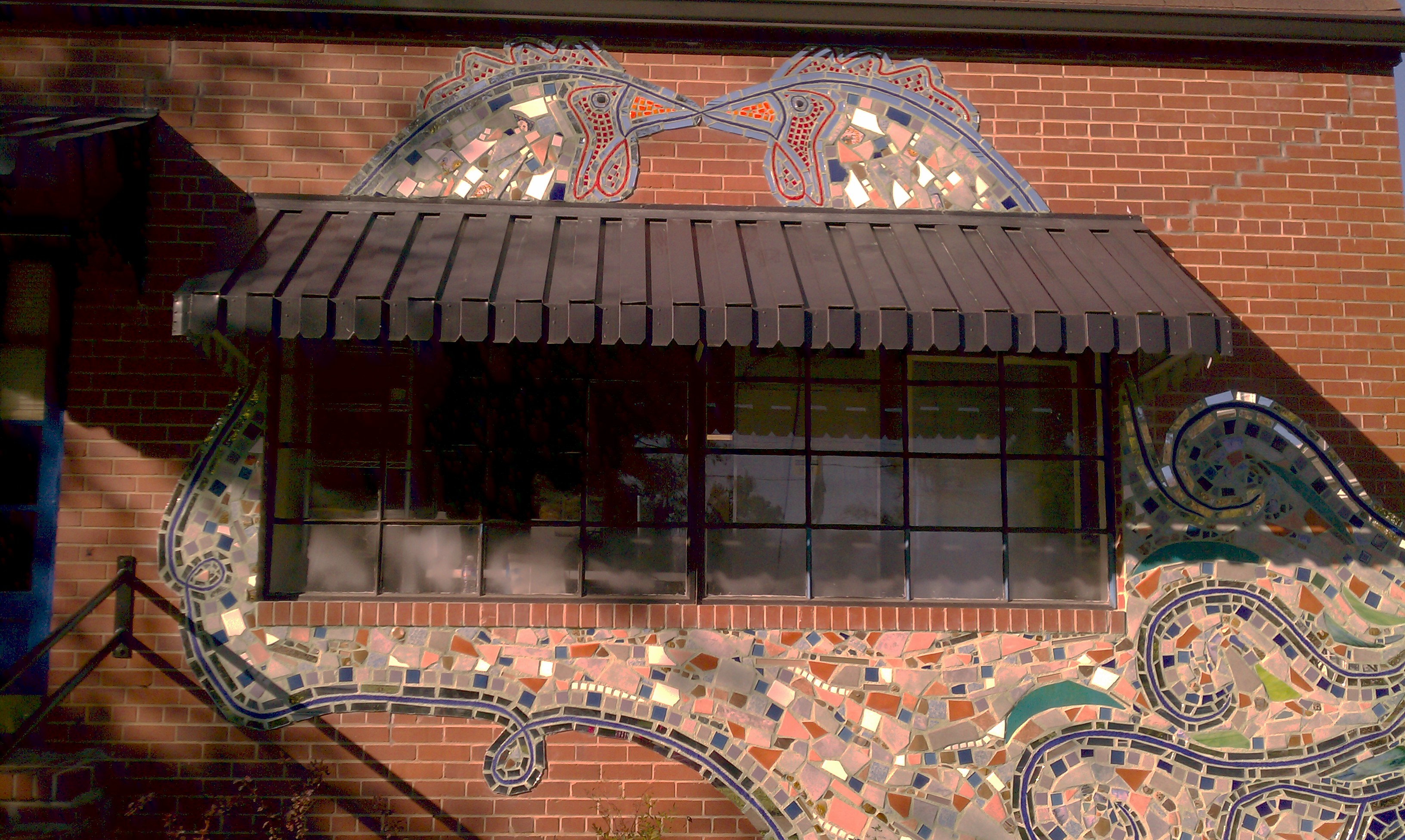 Lanelle Davis, a mosaic artist working in Pittsboro and Chapel Hill, NC, created this chicken mural on the wall of a building that had once been a hatchery.