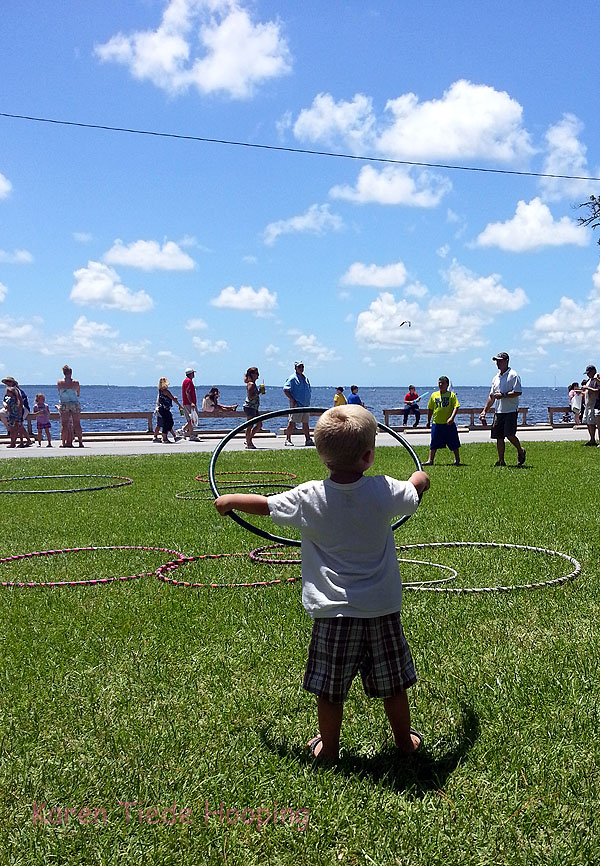 A little boy learns to hula hoop.