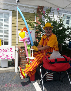 "John made up some balloon toys. The sign says, ""Bigger is Easier"" and refers to hula hoops."